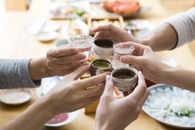 日本酒を持って乾杯する人たちの手