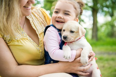 ラブラドールレトリーバーの子犬と少女と女性