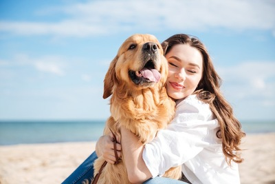 海を背景に砂浜で犬を抱きしめる女性