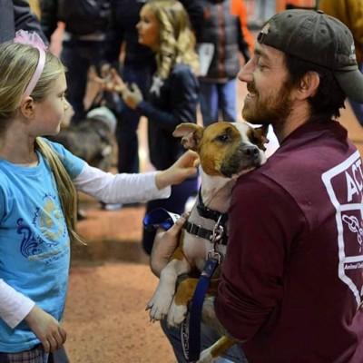 犬に触れる少女と笑顔の男性