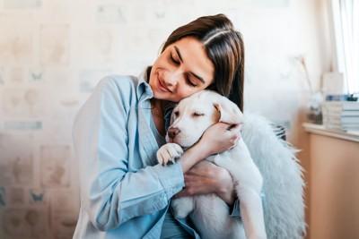 目を閉じて子犬を抱きしめている女性