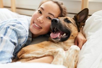 ベッドでくつろぐ女性と犬