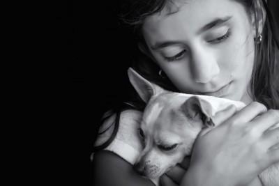 犬を抱きしめる悲しそうな女性