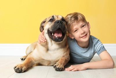 寄り添って床に寝そべる犬と男の子