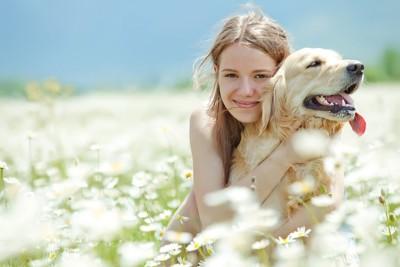 花畑にいる女性と犬