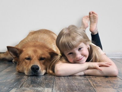 床に寝そべる犬と一緒に寝そべる笑顔の子供