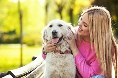 後ろから犬を撫でる笑顔の女性