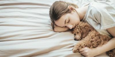 ベッドで一緒に眠る女性と犬