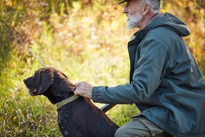 同じ方向を見つめるハンターと猟犬