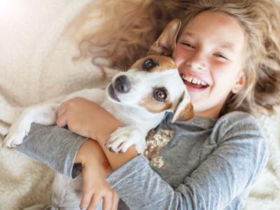 犬を抱きしめて寝転がる笑顔の少女