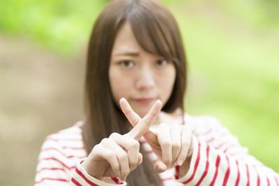 指でバツ印を作って拒絶する女性