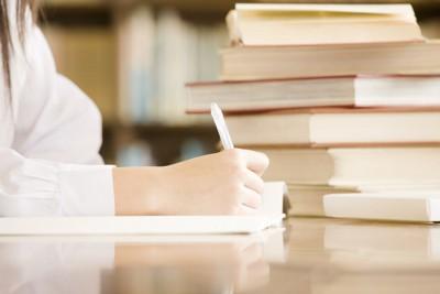 ペンを持つ手と積み上げられた本