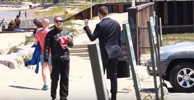 チワワを抱いた黒い服を着た男性と話すビジネスマン