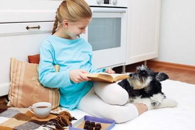 カーペットの上で寛ぐ女の子と犬
