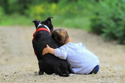 黒と白の犬に寄り掛かる子供