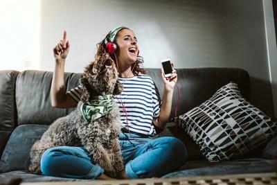ソファーに座って歌う犬と音楽を聴く女性