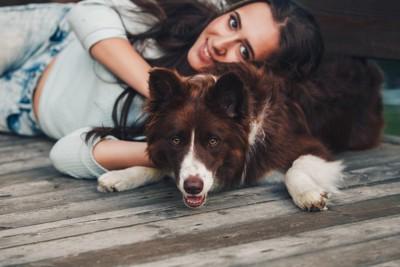 寝転がっている女性と犬