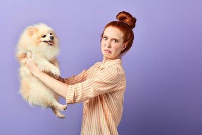 しかめっ面の女性と抱っこされる犬