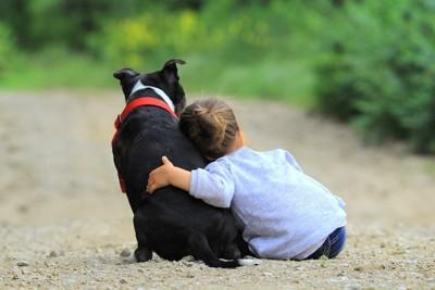 犬によりかかる子供の後ろ姿