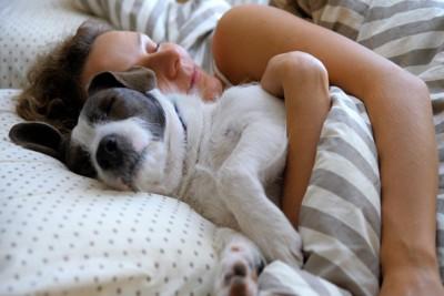 飼い主の女性と一緒に眠る犬