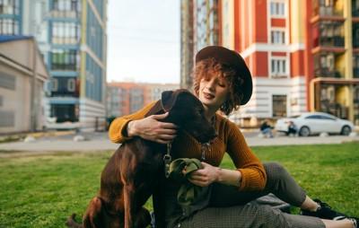 右手で犬の肩を抱いて座る女性