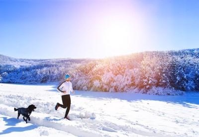 雪の中を走る男性と黒い犬