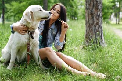 草むらに座る女性と犬