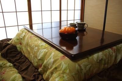 コタツとテーブルに置かれたミカン