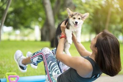 愛犬を抱き上げてヨガのポーズをとる女性