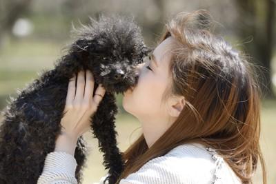 黒いトイプードルを抱き上げてキスする女性