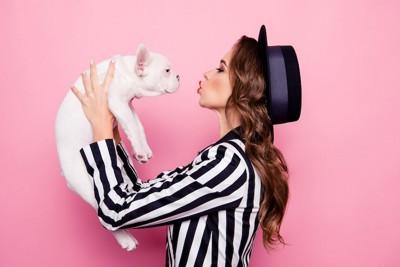 犬を抱き上げてキスしようとする女性