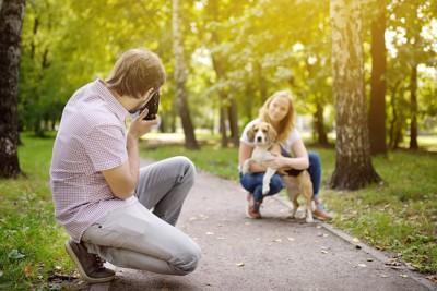 犬を抱えた女性を撮影する男性