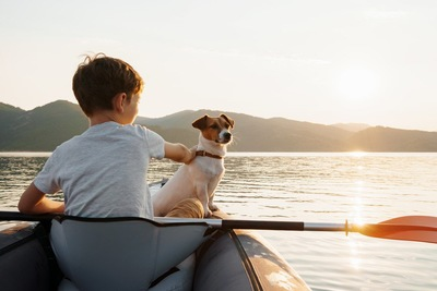 カヌーに乗っている犬と男の子