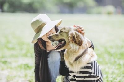 大型犬を撫でる帽子をかぶった女性