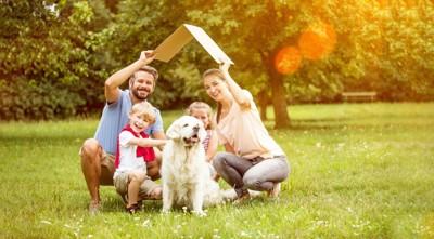 犬を中心にして芝生に集まる家族
