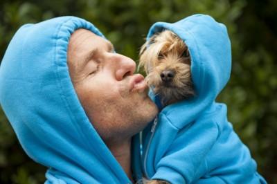 男性にキスされそうな犬