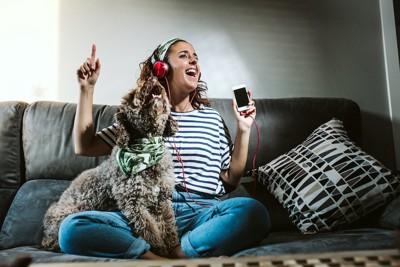 ソファーで歌う女性と一緒に遠吠えする犬