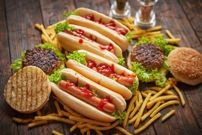 テーブルの上にあるたくさんのホットドッグとハンバーガーとポテト