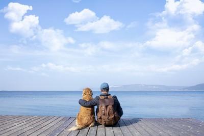 並んで座って海を見つめる男性と犬の後ろ姿