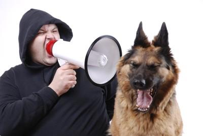 メガホンで怒鳴る男性と口を開ける犬