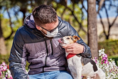 マスクを着けた男性と犬