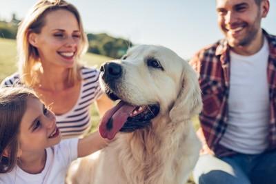 笑顔の家族の中心にいる犬