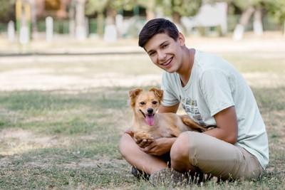 茶色い犬を抱くティーン男子