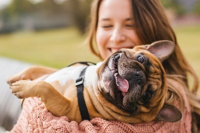 笑顔の犬を抱き上げる女性