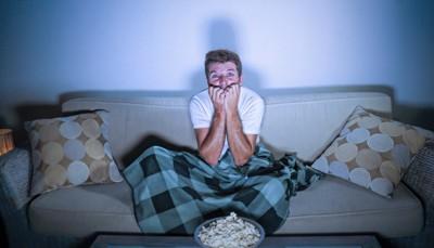 テレビを見ながら怖がっている男性