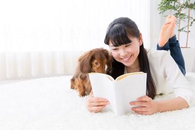 一緒に本を覗く犬と女性