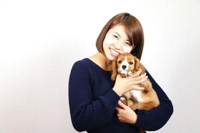 キャバリアの子犬を抱っこする女性