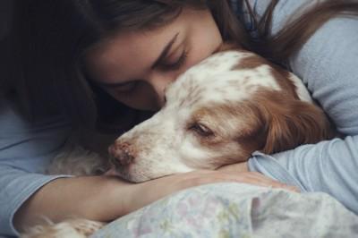 眠る犬を抱きしめる女性