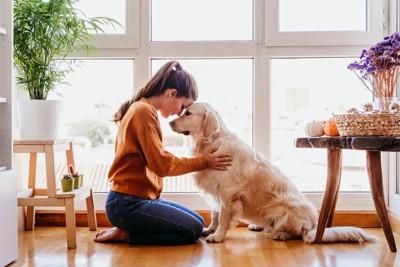 犬と頭をくっつけている女性