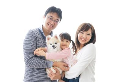 犬を抱いて笑顔の家族
